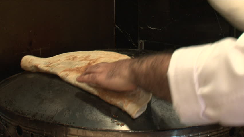 Markook Bread. Handheld shot of a cook baking an unleavened flatbread called Markook on a saj. Markook is popular in the countries of the Levant. (Dubai, UAE-2013)