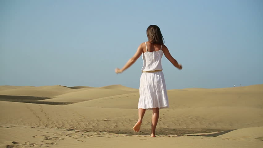 Young woman jumping in the desert, slow motion