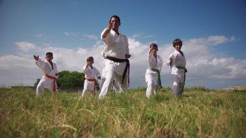 Young people, children, athletes, sport activity, combat and extreme sports, hispanic men exercising in karate and traditional martial arts. Simulation of fight on the beach near the sea