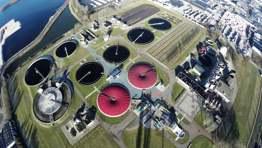 Aerial top down view flying over wastewater treatment plant also known as sewage treatment plant or sewage treatment works plant for sewage treatment process removing contaminants from wastewater 4k