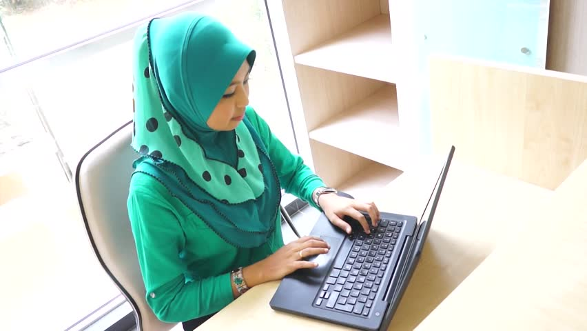 Young Muslim Girl using laptop and smile to the camera