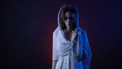 Ghost of lonely dead bride in white wedding dress and veil standing with sad face moving her hand. Scary girl halloween apperance make-up against horror background. Mysterious woman