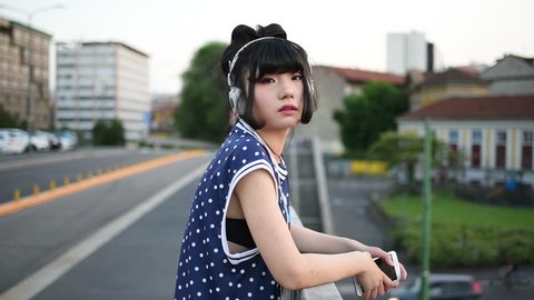 young beautiful asian millennial woman listening music with earphones and smart phone hand hold outdoor in city back light, looking at camera - relaxing, music, technology concept