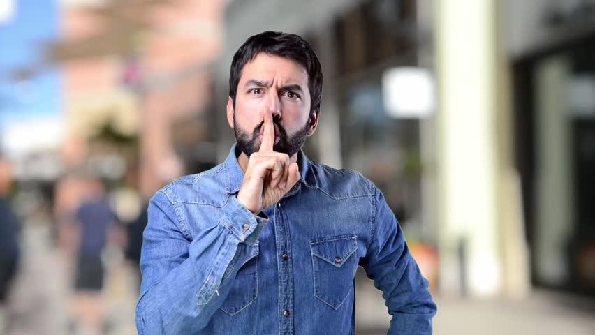 Handsome man making silence gesture on unfocused background   Shutterstock HD Video #22163485