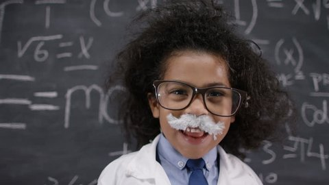 4K Happy little scientist with fake mustache writing math formulas on blackboard