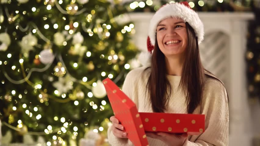 Happy Amazed Woman in Santa Hat, Holding Present in Her Hands, Opens It and Smiles. Pretty Brunette with Long Dark Hair and Santa Clause Cap Openning Christmas Gift Box Next to Xmas Tree