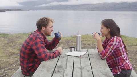 Camping people sitting at table drinking coffee from thermos bottle flask by lake on Iceland. Campers couple, woman and man relaxing taking break on road trip in beautiful Icelandic nature. 90 FPS.