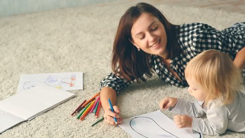 Baby girl draws a picture with pencils. Mother hugs and kisses her.