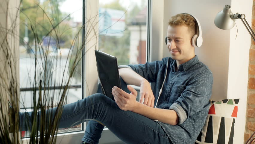 Happy man wearing headphones and having a videocall on tablet  | Shutterstock HD Video #22189762