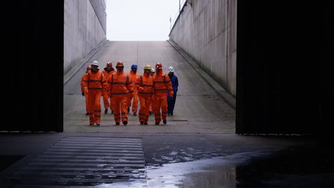 4K Workers at a fuel plant walking into darkness & preparing to go underground