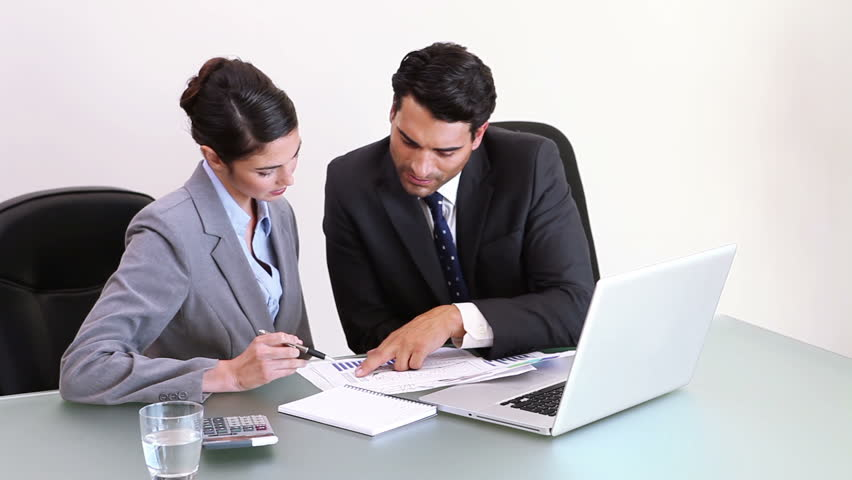 Business people working together while looking at charts in an office | Shutterstock HD Video #2219212