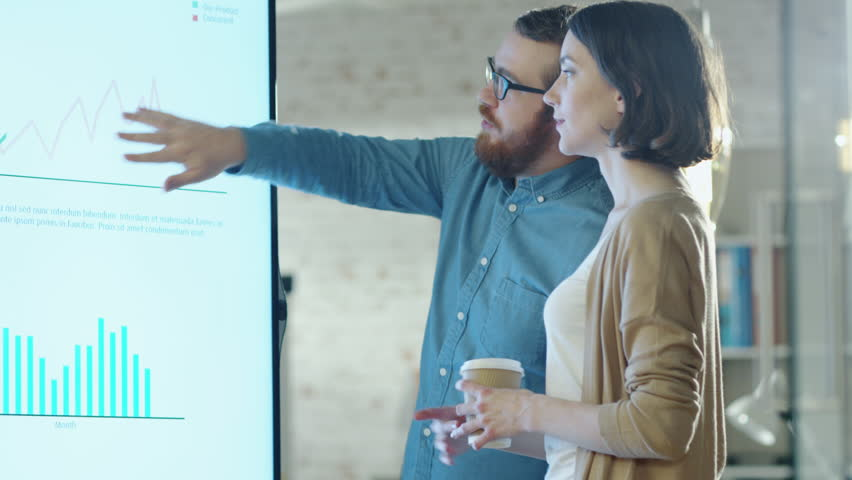 Young Man and Woman Discuss Charts Drawn on Their Electronic Whiteboard. Man Shows Details on the Screen Woman Listens Holding Cup of Coffee in Her Hands.Their Office is developer and Modern Looking. | Shutterstock Video #22195330