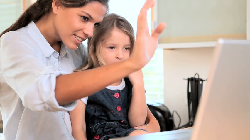 Mother and daughter talking on a video calling with a laptop in the kitchen | Shutterstock HD Video #2220463