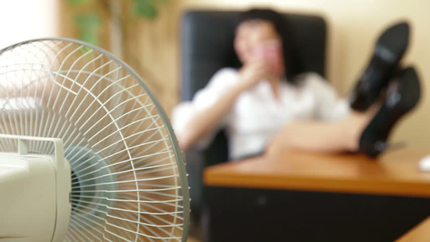 Relaxed Businesswoman With Feet On Table, Focus On The Fan