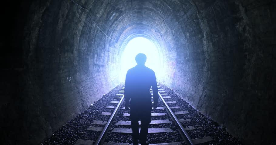 Man goes by railway tracks through dark tunnel toward bright light in the end #22209223