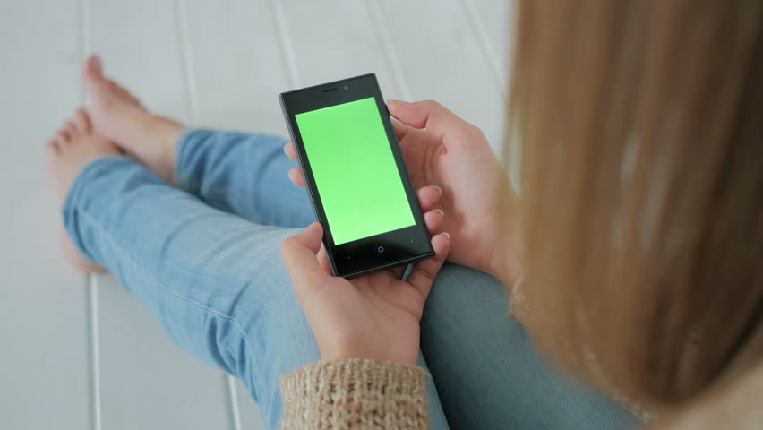 Woman sitting on the white wooden floor and using vertical smartphone with green screen. Close up shot of woman's hands with mobile Close up shot of woman's hands with mobile