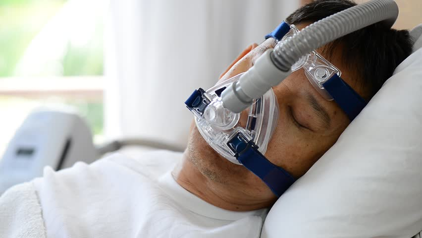 Close up of man upper body wearing cpap mask breathing and sleeping smoothly without snoring,side view . Obstructive sleep apnea therapy.