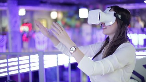 Young woman is happy in virtual reality glasses. VR. Shopping and entertainment center in the background.