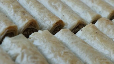 Panning on Turkish phyllo pie baklawa with walnuts close-up 4K 2160p 30fps UHD  footage - Arabic dessert filo dough sweet rolls baklava filled with nuts slow pan 3840X2160 UltraHD video