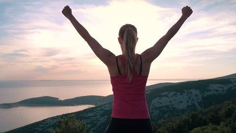 Slow motion - Young sporty female athlete raising arms victoriously after climbing the seaside mountain. Female model standing on top of the rock mountain in worship pose & celebrating successful hike