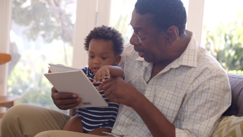 Grandfather And Grandson Reading Book At Home Together