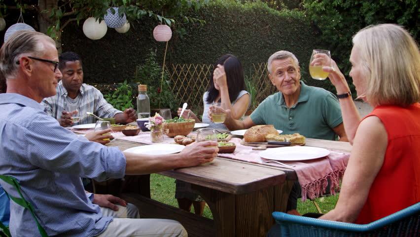 Mature Friends Enjoying Outdoor Meal In Backyard Shot On R3D | Shutterstock HD Video #22267852