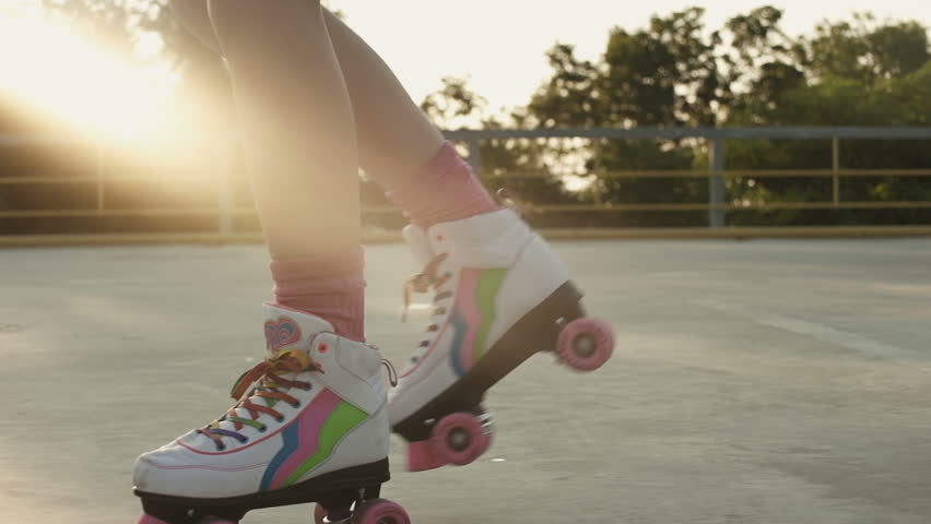 Female legs in roller blades skating fast at the playground