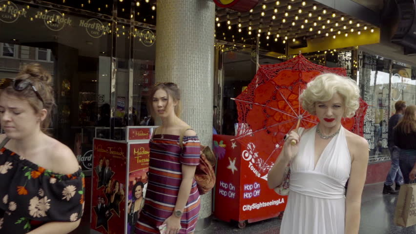LOS ANGELES - NOV 1, 2016: Marilyn Monroe Impersonator White Dress Red Umbrella Blowing Kiss And Posing For Camera Hollywood Blvd Los Angeles CA. Actors can be seen impersonating icons on the Blvd.