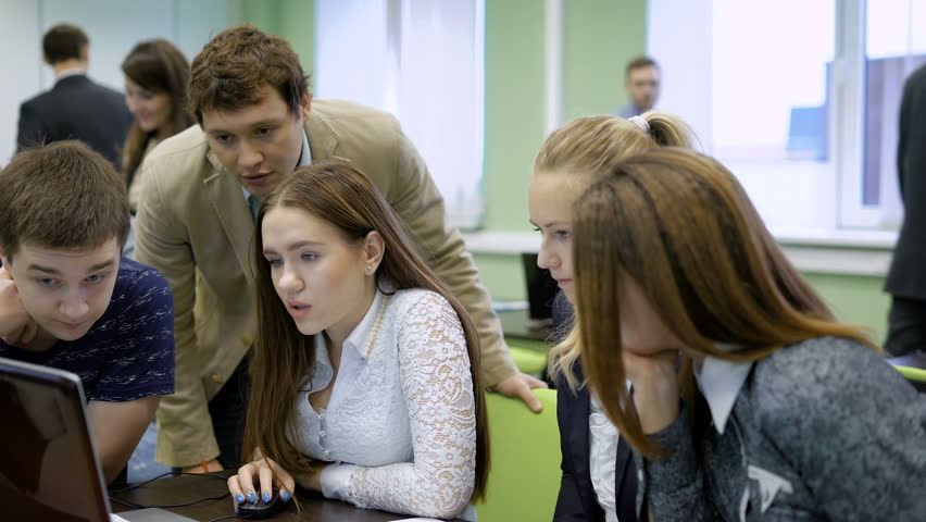 Group of people sitting at the table, carefully working with laptop in classroom and participating in business game and team building event. Girl in white blouse is looking at screen of PC #22330372