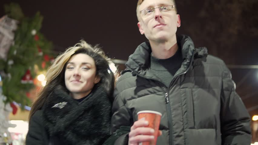 Young couple walk togerher near christmas lights at christmas market with a cup of warm tea | Shutterstock HD Video #22340392