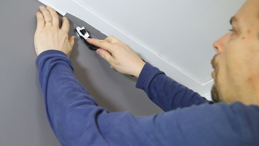 Cutting off the top of the wallpaper with a razor blade knife.