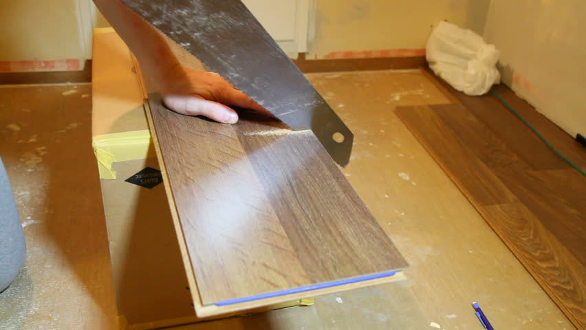 Man sawing a laminate floor plank.