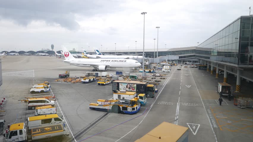 HONG KONG - APRIL 01, 2015: JAL airplane towed at ramp area, International airport terminal exterior. JAL JA613J aircraft (Boeing 767 - MSN 33849) slowly move and stop against modern terminal building