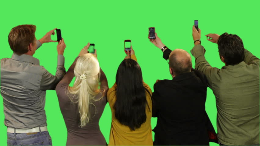 Crowd taking pictures on green screen
