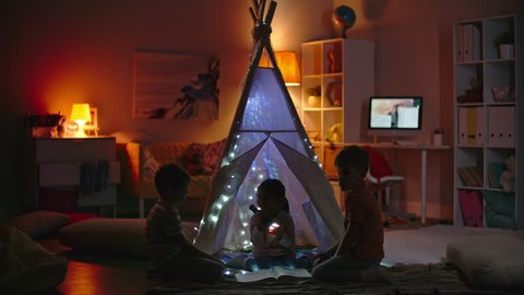 Little boys and girl with flashlight reading book at night in teepee decorated with fairy lights