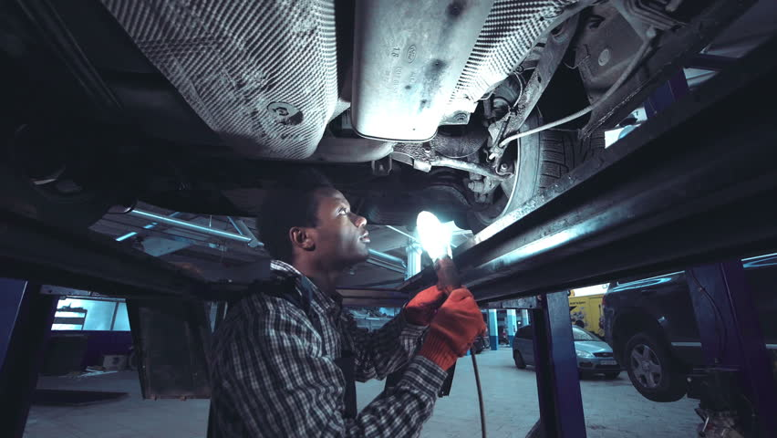 African mechanic working on the underside of a car elevated on a hoist shining a bright light onto the chassis