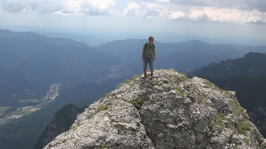 CARAIMAN MOUNTAINS, ROMANIA - Circa JULY 2016:Man on top of a cliff taking pictures.View of Busteni town, Romania, near to Heroes Cross , Caraiman Mountains, Romania, 4k, UHD | Shutterstock HD Video #22454677