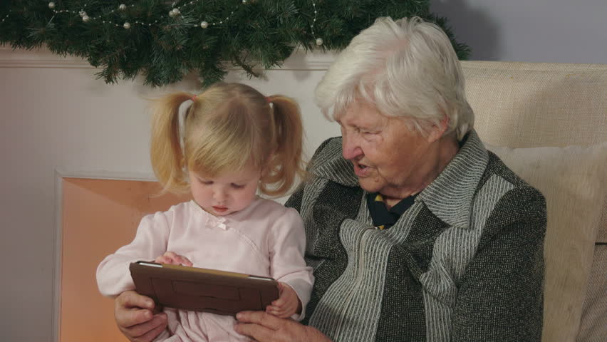 Little girl looking at the tablet photos while sitting on the lap of her grandmothe