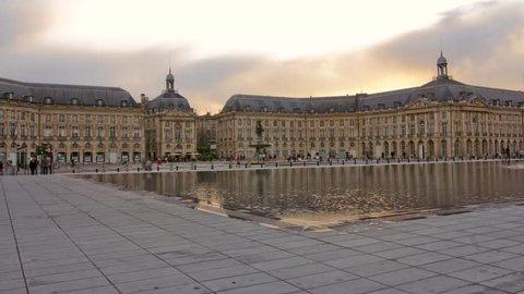Beautiful sunset: water mirror Bordeaux - Place and Palais de la Bourse and miroir d'eau in France, Hyperlapse Timelapse, ancient meets modern architecture, cloudy sky