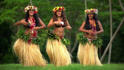 Polynesian girls in traditional grass skirts and flower headdress dancing hula style while entertaining barefoot outdoors Tahiti French Polynesia South, Pacific,