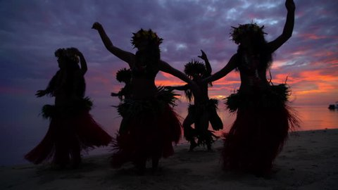 Young males and females in a group of Tahitian hula dancers performing at sunset on the beach barefoot in traditional costume Tahiti French Polynesia South Pacific