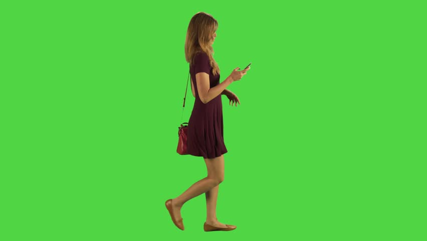 Young woman walking sideways and texting in a full body shot over a green screen. | Shutterstock HD Video #22489942