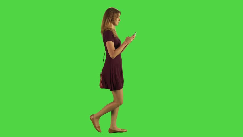 Young woman walking sideways and texting happily in a full body shot over a green screen. Two takes. | Shutterstock HD Video #22490002