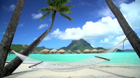 Beach palm trees hammock Overwater luxury Bungalows in tropical Aquamarine lagoon a Tahitian vacation resort of Bora Bora South Pacific