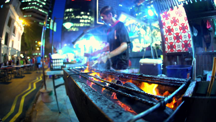 Singapore - September 2016: Male cooking traditional Asian chicken kebab street food outdoor on a coal barbecue fire at night in Asian Food Market South East Asia | Shutterstock HD Video #22497412