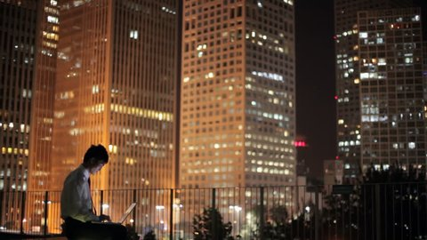 WS Businessman sitting on terrace using laptop, cityscape in background at night / Beijing, China