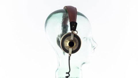 a clear glass mannequin head with amazing changing collection of vintage headphones spinning on a rotary turntable