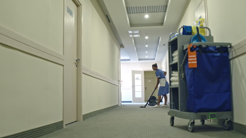 PAN of Latin American cleaning service lady in uniform vacuuming carpet in hotel hall