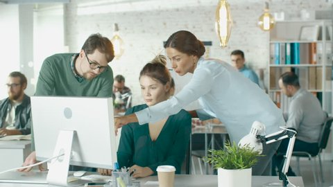 Young  Man and Two Women Stand before Computer Desk in a Creative Office. They Discuss Business Issues. Diverse People Working in Background.  Shot on RED EPIC (uhd).