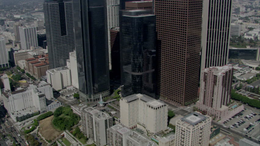 Aerial flying shot over and between skyscrapers in Los Angeles downtown area circa 2009